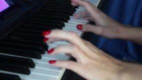 το κορίτσι 2 χεριών δοκιμάζει το πιάνο παιχνιδιού φιλμ μικρού μήκους