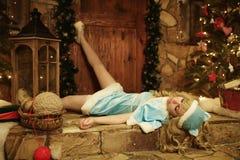 Το κορίτσι χιονιού βρίσκεται και wriggles στο κατώφλι του σπιτιού που διακοσμείται στο ύφος Χριστουγέννων Στοκ εικόνα με δικαίωμα ελεύθερης χρήσης