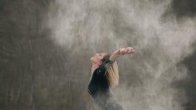 Το κορίτσι χορευτών που ντύνεται στο μαύρο κοστούμι σωμάτων εκτελεί το σύγχρονο χορό στο πάτωμα, κάνει το κτύπημα με την τρίχα απόθεμα βίντεο