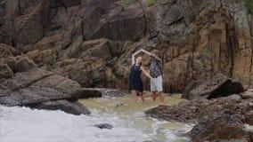 Το κορίτσι χορεύει στην ακτή του ωκεανού και κρατά το άτομο από το χέρι, σε αργή κίνηση Όμορφη άποψη της παραλίας θάλασσας απόθεμα βίντεο