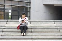 Το κορίτσι χρησιμοποιεί ένα τηλέφωνο Στοκ Εικόνες