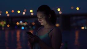 Το κορίτσι χρησιμοποιεί ένα smartphone περπατώντας σε μια παραλία νύχτας HD απόθεμα βίντεο