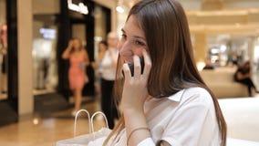 Το κορίτσι χρησιμοποιεί το τηλέφωνο στη συνεδρίαση λεωφόρων σε έναν πάγκο φιλμ μικρού μήκους