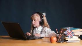 Το κορίτσι χρησιμοποιεί το lap-top φιλμ μικρού μήκους