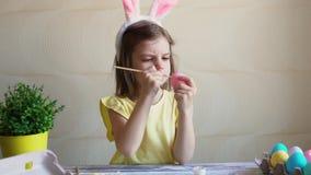 το κορίτσι χρωματίζει τα αυγά Πάσχας