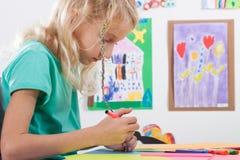 Το κορίτσι χρωματίζει τους δείκτες για τα μαθήματα τέχνης Στοκ Φωτογραφίες