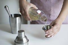 Το κορίτσι χύνει το ποτό από το μπουκάλι σε ένα μετρώντας ποτήρι Στοκ Εικόνες