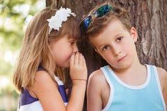 Το κορίτσι ψιθυρίζει ένα μυστικό σε ένα αυτί αγοριών στοκ εικόνες