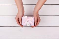 το κορίτσι δώρων δίνει Θηλυκό χέρι που κρατά ένα δώρο με ένα τόξο Στοκ φωτογραφία με δικαίωμα ελεύθερης χρήσης