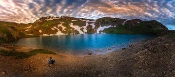 Το κορίτσι Backpacker κάθεται από τη λίμνη Como Κολοράντο ΗΠΑ στοκ εικόνα