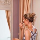 Το κορίτσι Beautful στέκεται μπροστά από έναν καθρέφτη βάζοντας σε Makeup Στοκ φωτογραφία με δικαίωμα ελεύθερης χρήσης