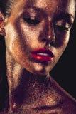Το κορίτσι Beautyful με το χρυσό ακτινοβολεί στο πρόσωπό της Στοκ Εικόνες