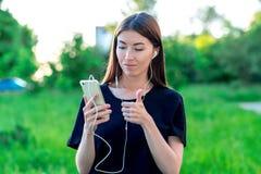 Το κορίτσι brunette το καλοκαίρι σε ένα πάρκο στη φύση Μια τηλεοπτική κλήση επικοινωνεί πέρα από το τηλέφωνο Κρατά τα χέρια με έν Στοκ Εικόνες