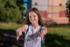 Το κορίτσι brunette Το καλοκαίρι στην πόλη στη φύση Μια μαθήτρια μετά από τα μαθήματα πίσω από το σακίδιο πλάτης της Χέρια χειρον Στοκ Φωτογραφία