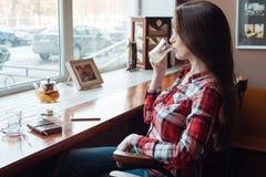 Το κορίτσι brunette με τα ποτήρια και ένα πουκάμισο, το απόγευμα σε έναν καφέ από το παράθυρο, πίνουν το τσάι το πρωί Δίπλα Στοκ φωτογραφίες με δικαίωμα ελεύθερης χρήσης