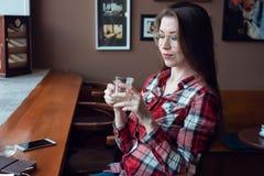 Το κορίτσι brunette με τα ποτήρια και ένα πουκάμισο, το απόγευμα σε έναν καφέ από το παράθυρο, πίνουν το τσάι το πρωί Δίπλα Στοκ φωτογραφία με δικαίωμα ελεύθερης χρήσης