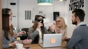 Το κορίτσι Brunette δοκιμάζει app για τα γυαλιά εικονικής πραγματικότητας κρανών VR οι φίλοι και οι συνάδελφοί της που υποστηρίζο Στοκ Εικόνες