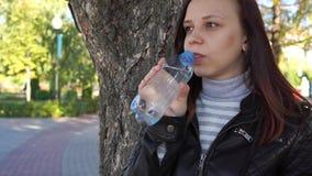 Το κορίτσι Brunette πίνει το πόσιμο νερό από το μπουκάλι στο πράσινο θερινό πάρκο Υγιής τρόπος ζωής Έννοια καθαρού νερού κατανάλω φιλμ μικρού μήκους