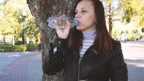 Το κορίτσι Brunette πίνει το πόσιμο νερό από το μπουκάλι στο πράσινο θερινό πάρκο Υγιής τρόπος ζωής Έννοια καθαρού νερού κατανάλω απόθεμα βίντεο