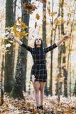 Το κορίτσι brunette που ρίχνει τα φύλλα που απολαμβάνουν προς τα πάνω το autum Στοκ εικόνες με δικαίωμα ελεύθερης χρήσης