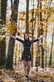 Το κορίτσι brunette που ρίχνει τα φύλλα που απολαμβάνουν προς τα πάνω το autum Στοκ φωτογραφίες με δικαίωμα ελεύθερης χρήσης
