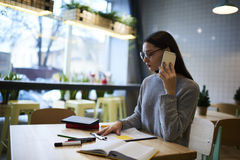 Το κορίτσι brunette στα γυαλιά εκτελεί την καθημερινή εργασία οργανώνοντας την εργασία των πελατών προσωπικού και συνεδρίασης της στοκ εικόνα