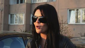 Το κορίτσι Brunette στα γυαλιά ηλίου τραγουδά κεκλεισμένων των θυρών στο σπίτι στην οδό το θερινό ηλιόλουστο βράδυ μαύρο σακάκι απόθεμα βίντεο