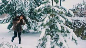 Το κορίτσι Brunette στο καφετί παλτό γουνών βουρτσίζει το χιόνι από τον κλάδο του χριστουγεννιάτικου δέντρου σε αργή κίνηση απόθεμα βίντεο