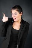 Το κορίτσι Brunette στο παλτό εμφανίζει μεγάλο δάχτυλο Στοκ Φωτογραφίες