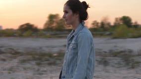 Το κορίτσι Brunette στο σακάκι τζιν είναι στη χέρσα περιοχή φιλμ μικρού μήκους