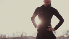 Το κορίτσι Brunette στο στάδιο εκτελεί στον ήλιο τις ασκήσεις ικανότητας απόθεμα βίντεο