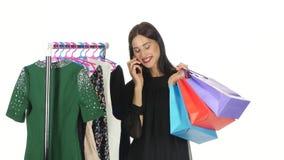 Το κορίτσι Brunette ψωνίζει για τα φορέματα μιλώντας στο τηλέφωνο σε ένα πολυκατάστημα άσπρος φιλμ μικρού μήκους