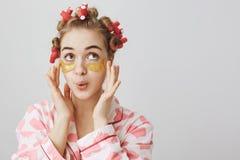 Το κορίτσι Girly στα τρίχα-ρόλερ και οι πυτζάμες με την τυπωμένη ύλη καρδιών που εφαρμόζει το μπάλωμα ματιών καλύπτουν και που αν στοκ φωτογραφία