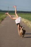 το κορίτσι handstand κάνει τις νεολαίες κουταβιών Στοκ Εικόνες