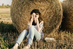 Το κορίτσι hipster συγκεχυμένα καλύπτει το πρόσωπο ενάντια στο δέμα σανού Στοκ εικόνες με δικαίωμα ελεύθερης χρήσης