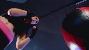 Το κορίτσι kickboxer επιλύει τα χτυπήματα στο αχλάδι στη γυμναστική απόθεμα βίντεο