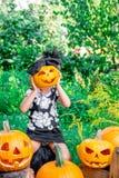 Το κορίτσι Litlle κρατά την κολοκύθα αποκριών μπροστά από το πρόσωπό της Το παιδί που ντύνεται στο Μαύρο η διακόσμηση Jack-ο-φανα Στοκ εικόνα με δικαίωμα ελεύθερης χρήσης
