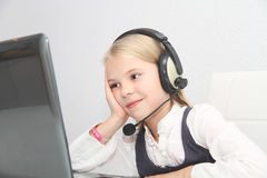 Το κορίτσι Llittle κάθεται μπροστά από ένα lap-top με τα ακουστικά και μαθαίνει Στοκ Εικόνες