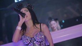 Το κορίτσι MC στο αυτί ποντικιών, αποδίδει στη σκηνή nightclub κίνηση αργή DJ στο υπόβαθρο φιλμ μικρού μήκους