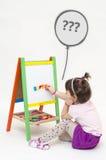 Το κορίτσι Musingly κολλά τις μαγνητικές επιστολές άσπρο να αναρωτηθεί πινάκων Στοκ Φωτογραφία