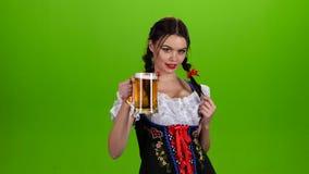 Το κορίτσι Oktoberfest προσελκύει σεξουαλικά και γλείφει τα χείλια του πράσινη οθόνη απόθεμα βίντεο