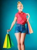 Το κορίτσι Pinup με τις αγορές τοποθετεί τα ενδύματα αγοράς σε σάκκο. Πώληση Στοκ Φωτογραφία