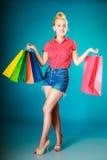 Το κορίτσι Pinup με τις αγορές τοποθετεί τα ενδύματα αγοράς σε σάκκο. Πώληση Στοκ εικόνα με δικαίωμα ελεύθερης χρήσης