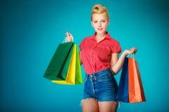 Το κορίτσι Pinup με τις αγορές τοποθετεί τα ενδύματα αγοράς σε σάκκο Πώληση Στοκ φωτογραφίες με δικαίωμα ελεύθερης χρήσης