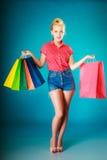 Το κορίτσι Pinup με τις αγορές τοποθετεί τα ενδύματα αγοράς σε σάκκο Πώληση Στοκ Εικόνα