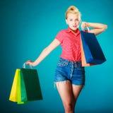 Το κορίτσι Pinup με τις αγορές τοποθετεί τα ενδύματα αγοράς σε σάκκο Πώληση Στοκ εικόνα με δικαίωμα ελεύθερης χρήσης