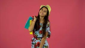 Το κορίτσι Shopaholic με τις τσάντες στα χέρια της στέκεται και αρχίζει Ρόδινη ανασκόπηση φιλμ μικρού μήκους