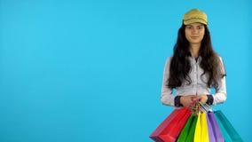 Το κορίτσι Shopaholic με τις τσάντες στα χέρια της στέκεται και αρχίζει πρόσκληση συγχαρητηρίων καρτών ανασκόπησης απόθεμα βίντεο