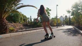 Το κορίτσι skateboard στα κοντά σορτς οδηγά στο δρόμο κατά μήκος της παραλίας και των φοινίκων φιλμ μικρού μήκους