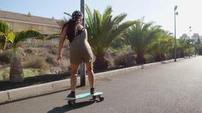 Το κορίτσι skateboard στα κοντά σορτς οδηγά στο δρόμο κατά μήκος της παραλίας και των φοινίκων απόθεμα βίντεο